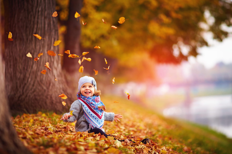 Une fillette joue avec les feuilles